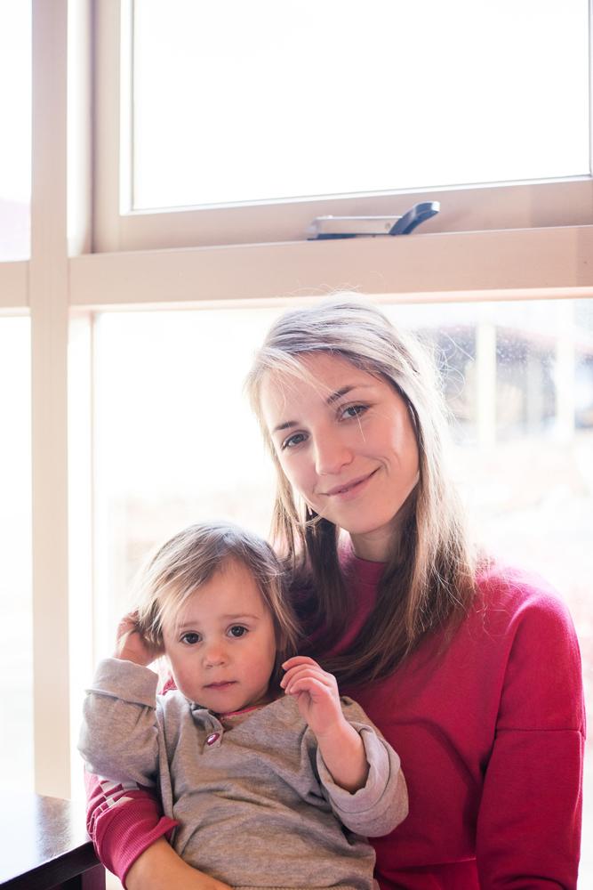 Dunkelblonde Frau mit kleinem Mädchen im Cafe