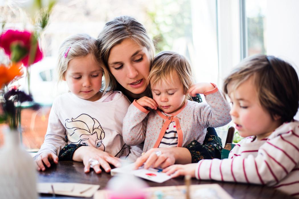 Dunkelblonde Frau liest kleinen kleinen Kindern ein Buch im Café vor
