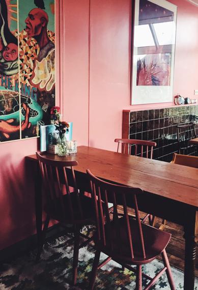 Rosa und grüne Einrichtung im Café mit dunklen Holzmöbeln und schwarzen Fliesen