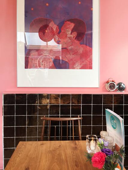 Rosafarbene Wand mit schwarzen Fliesen und Holztisch und Bild