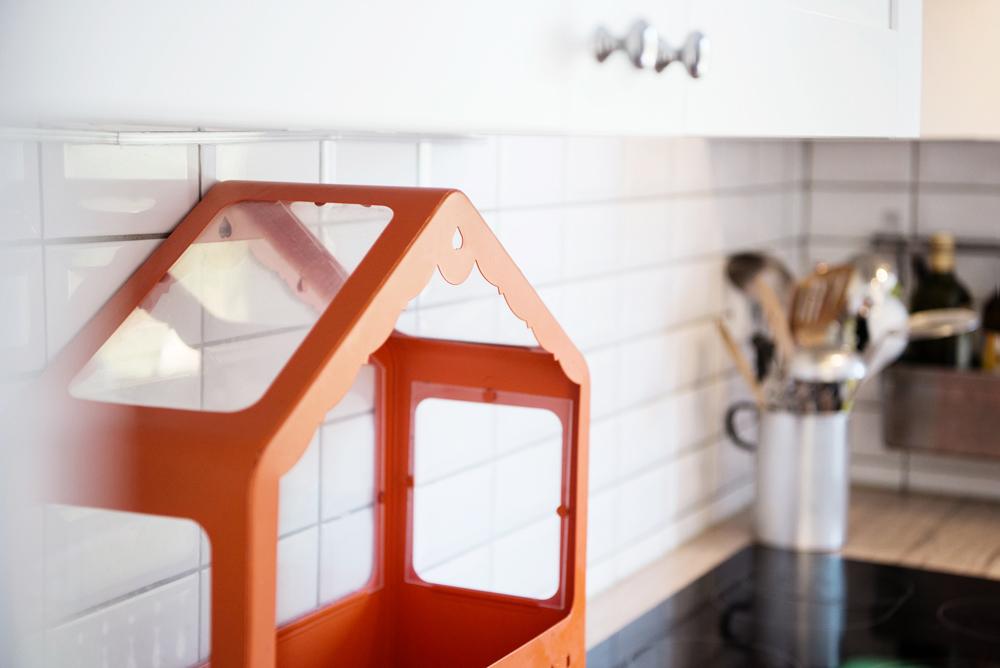Orangefarbenes Gewächshaus für Kräuter vor weißen Metrofliesen in der Küche