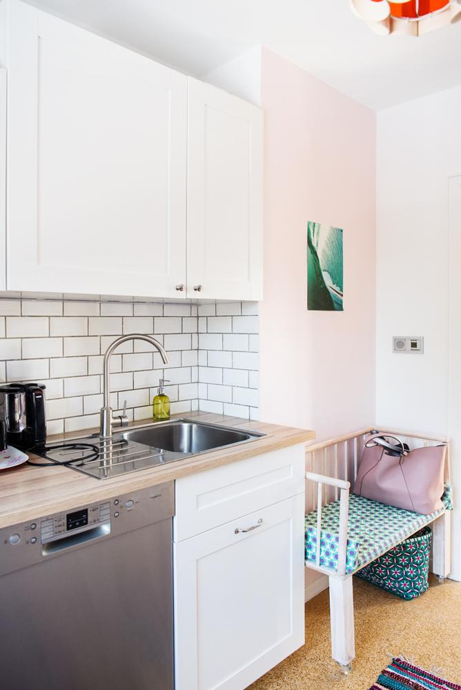 Rosa Wandfarbe, weiße Küchenzeile und Metrofliesen in weiß mit Surferbild