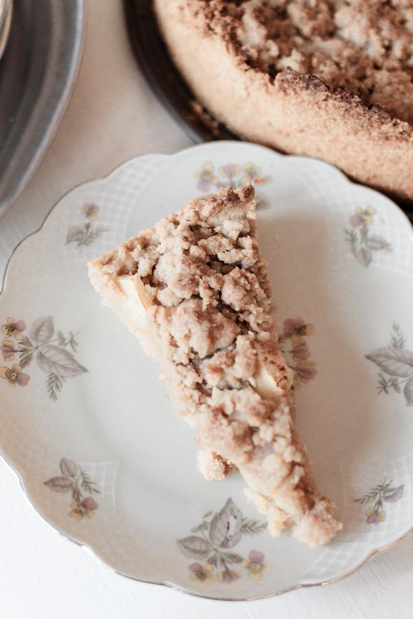 Stück von einem Apfelstreuselkuchen mit Sahne auf einem Teller auf einem weißen Tisch