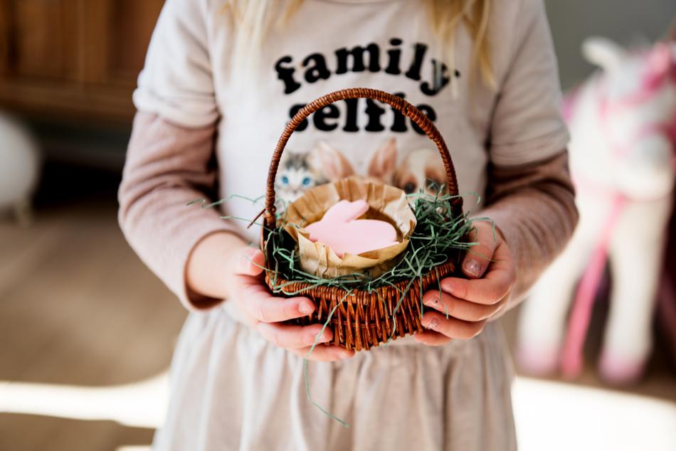 Blondes Mädchen mit einem Osterkörbchen mit Osterhase in den Händen
