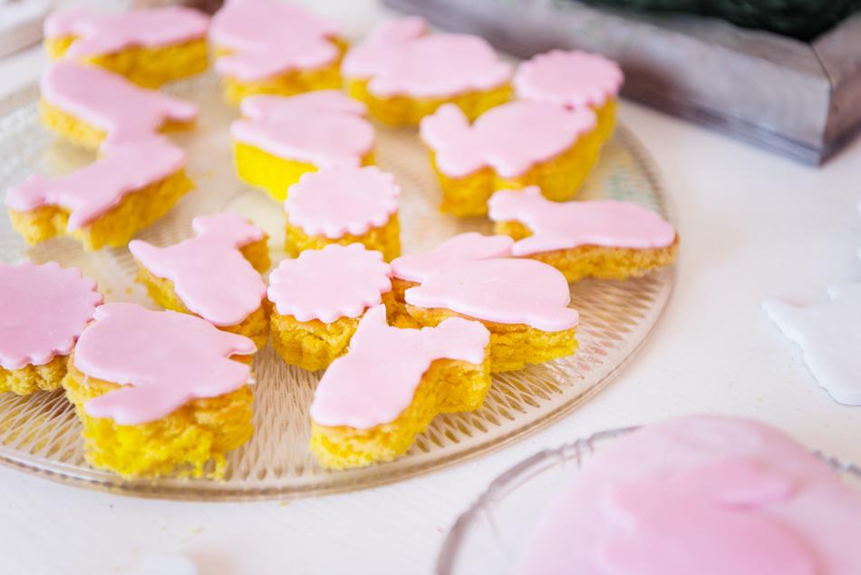 Kuchenplatte zu Ostern mit selbstgebackenem Ostergebäck in gelb und rosa Fondantteig