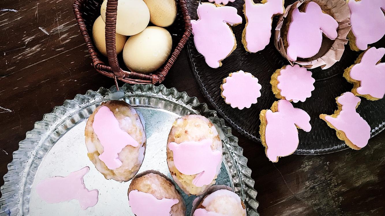 Rosa Herzkuchen mit Osterhase, Ostereier mit Osterlamm und Osterhasenverzierung als Dekoration auf einem Spiegeltablett auf braunem Holztisch