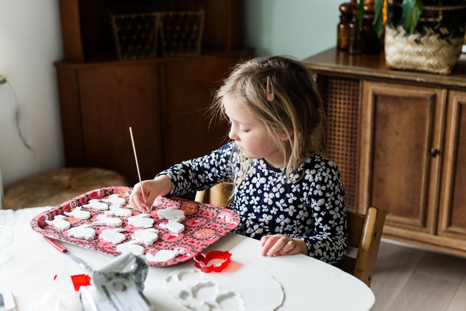 Blondes Mädchen bastelt am Tisch mit Modelliermasse und sticht Ostermotive aus