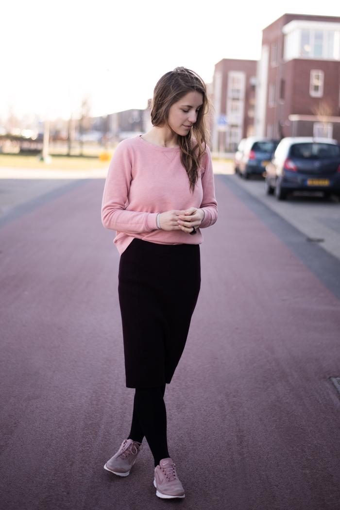 Braunhaarige Frau im Bleistiftrock, rosa Sweater, rosa Turnschuhen in Holland auf der Straße während des Internationalen Frauentages