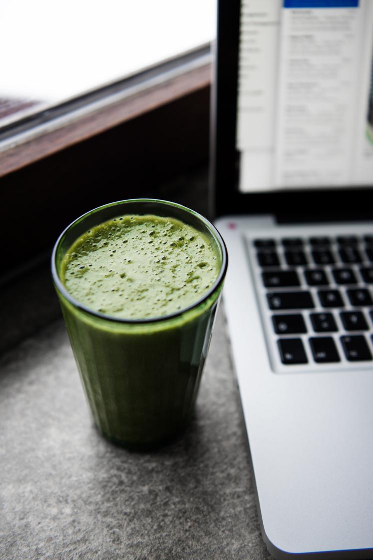 Grüner Smoothie mit Feldsalat,Gurke, Spinat, Mandarine und Banane im Glas am Laptop auf einer Fensterbank aus Stein