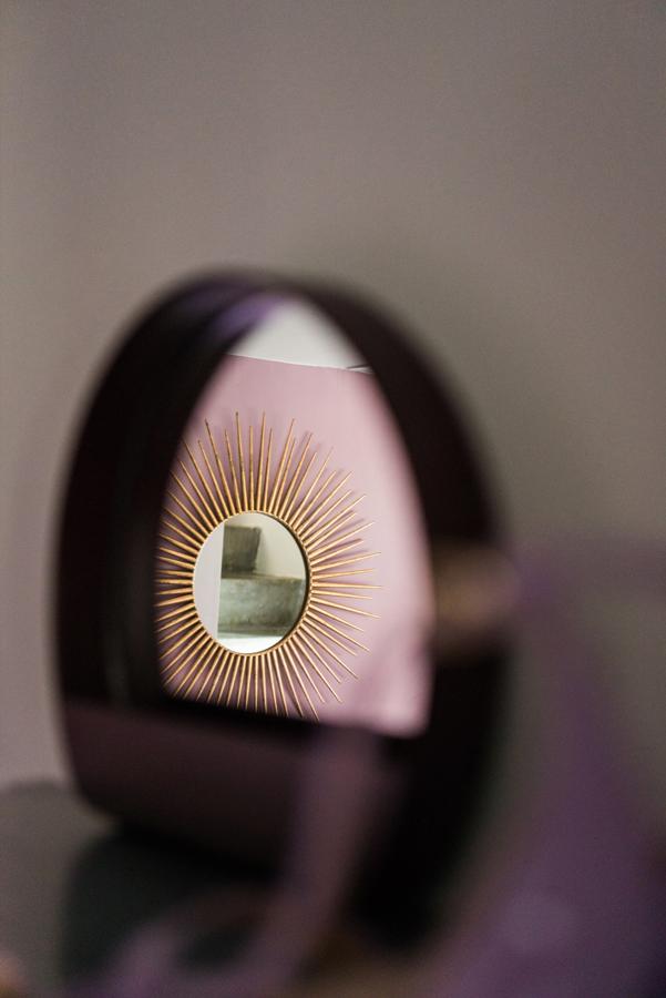 Kleiner Spiegel in bordeaux mit Sonnenspiegel in der Spiegelung