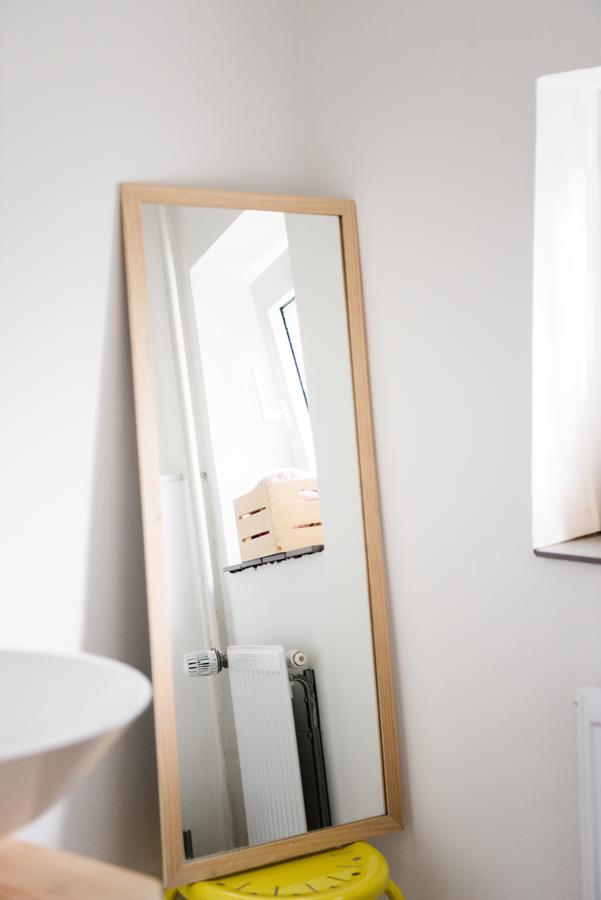 Länglicher Spiegel mit Holzrahmen steht auf einem Hocker in einem hellen Badezimmer