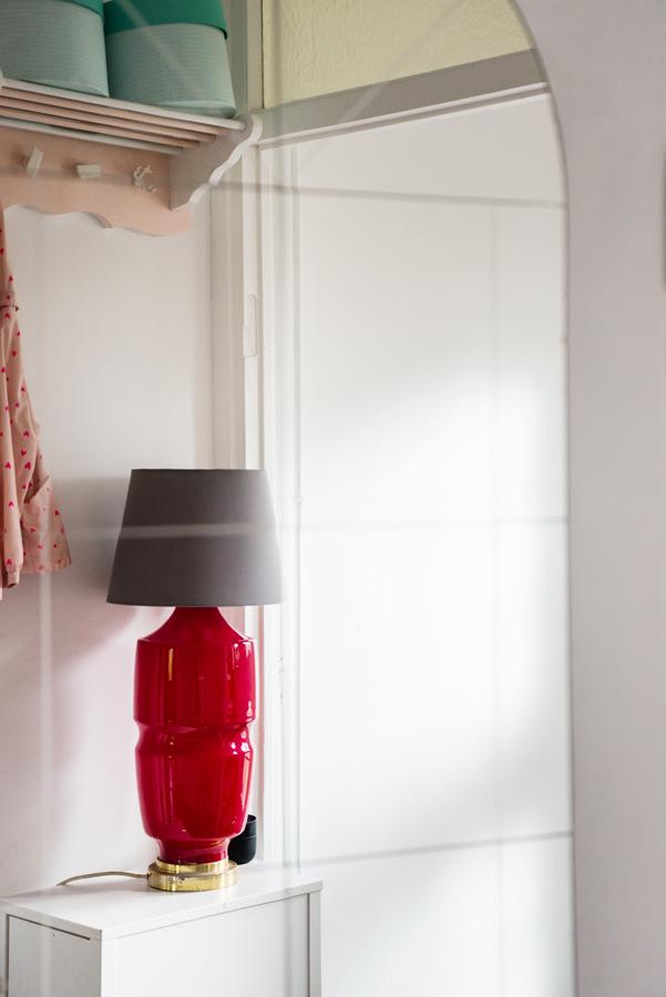 Spiegel im Eingangsbereich mit Stehlampe mit rotem Fuß und grauem Schirm