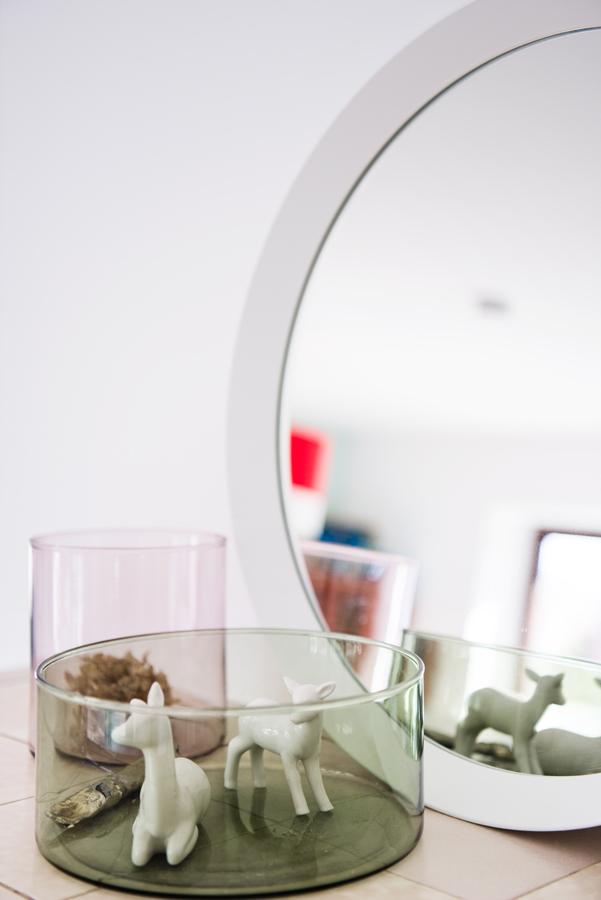 Großer runder weißer Spiegel mit Dekoration davor