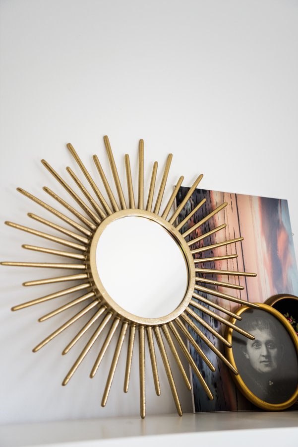 Sonnenspiegel steht auf einem Regal neben Bildern