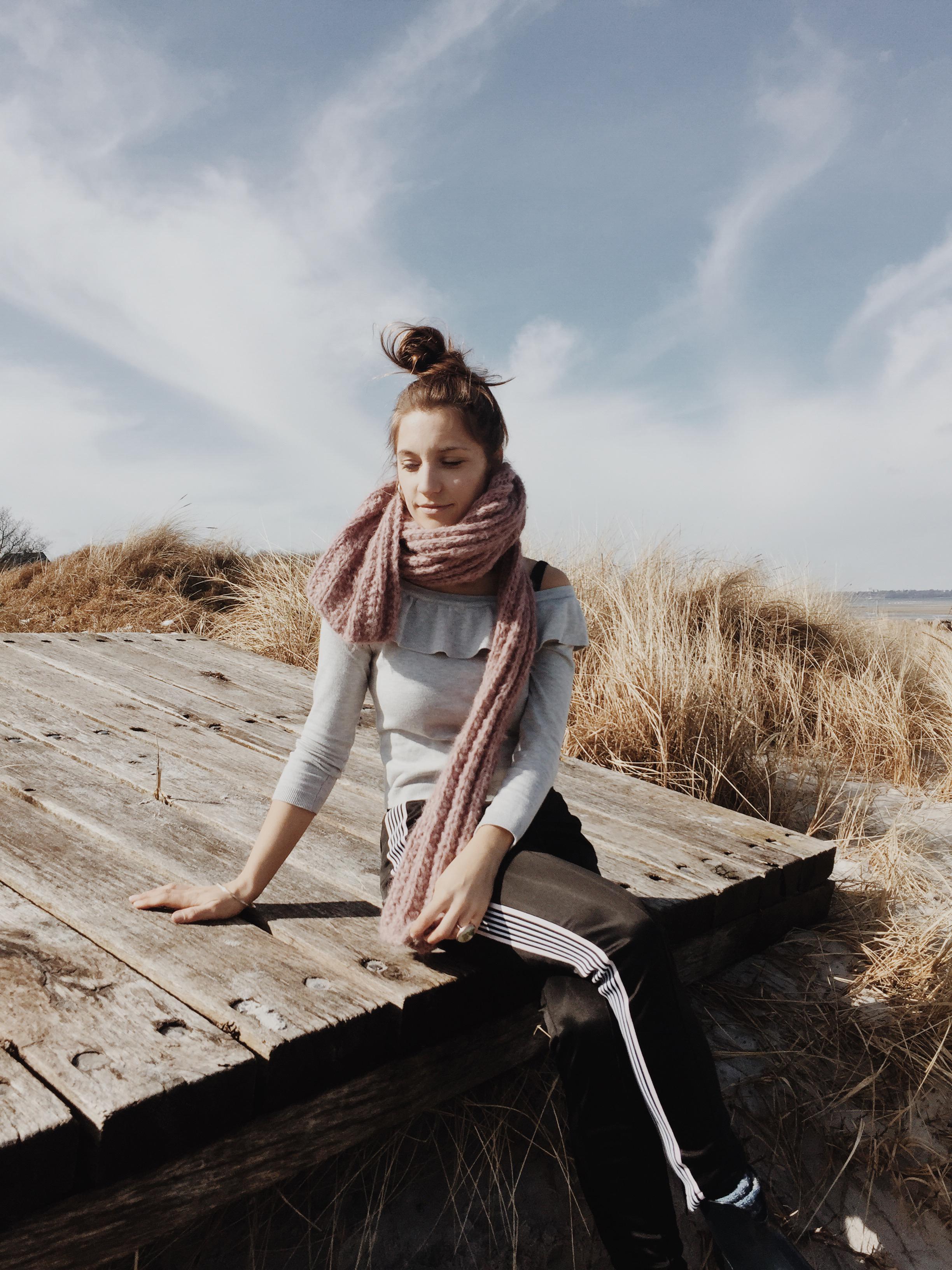 Frau am Strand mit Jogginghose, grauem Shirt, Dutt und Stiefeln in Stein mit der Ostsee im Hintergrund