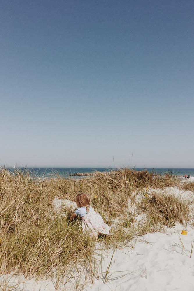 Blondes Mädchen in den Dünen am Strand an der Ostsee