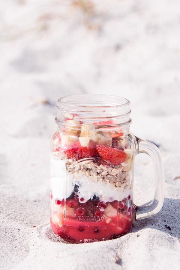 Obstjoghurt mit Haferflocken geschichtet im Glas auf einer rosafarbenen Decke am Strand