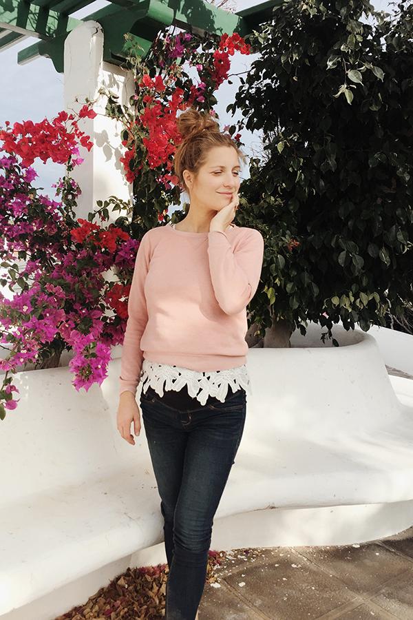Selbstständige Frau mit Dutt und apricotfarbenem Pullover steht vor Blumen auf Teneriffa
