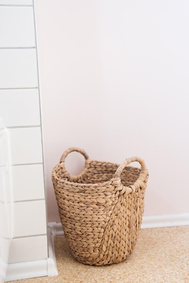 Helles Badezimmer mit weißen schmalen Fliesen, rosafarbener Wand und Naturmaterialien, Korb aus Seegras