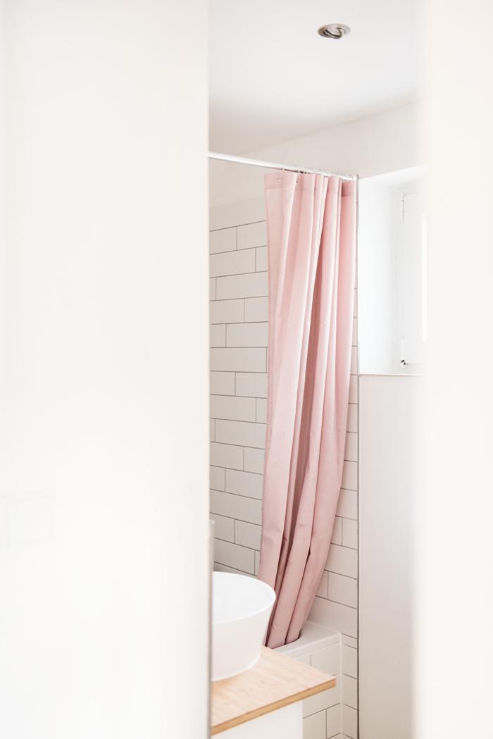 Helles Badezimmer mit weißen Fliesen, Duschwanne, Aufsatzwaschbecken und rosafarbenen Duschvorhang