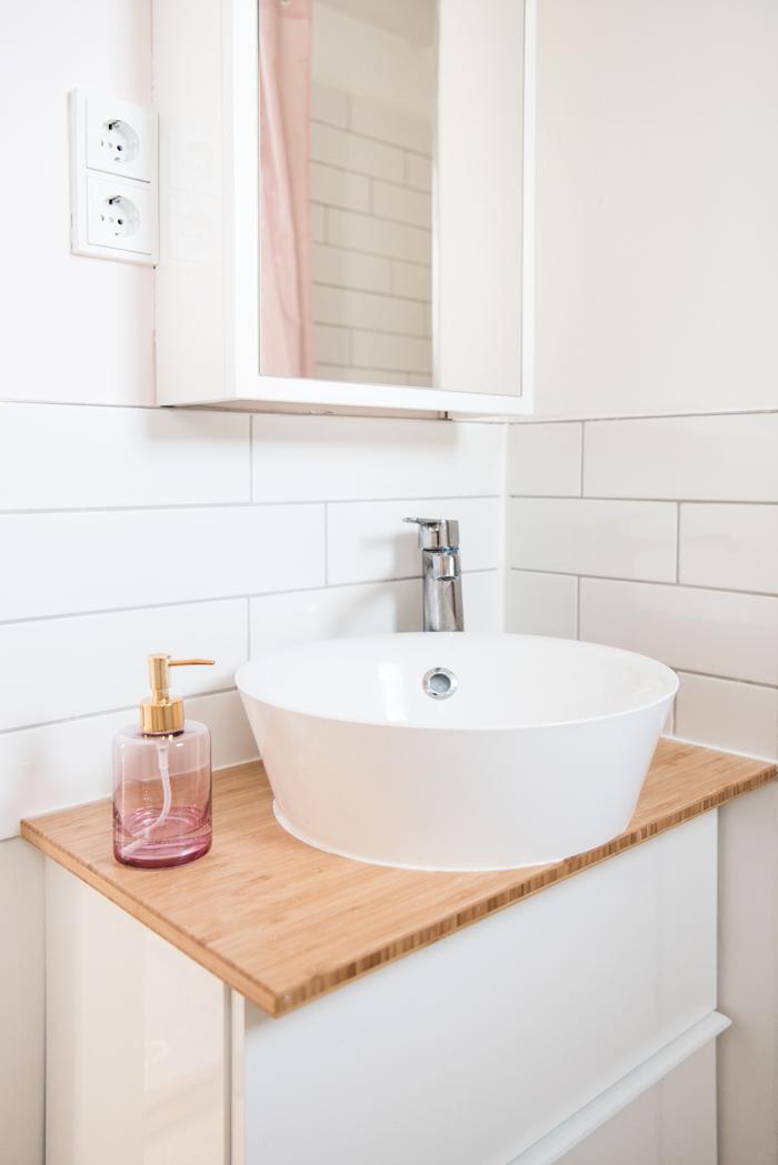 Rosafarbener Glasseifenspender mit goldenem Kopf steht auf Bambuswaschtisch mit Aufsatzwaschbecken im hellen Bad mit weißen Fliesen