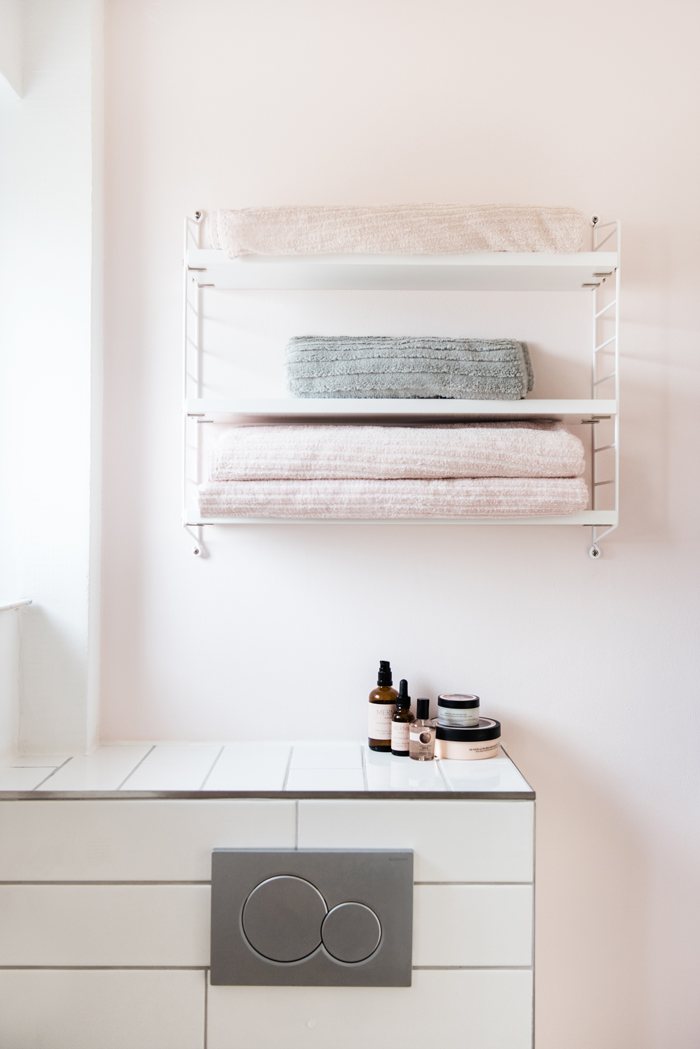 Helles Badezimmer mit weißen schmalen Fliesen, rosafarbener Wand mit weißem String-Regal und Unterputz-WC