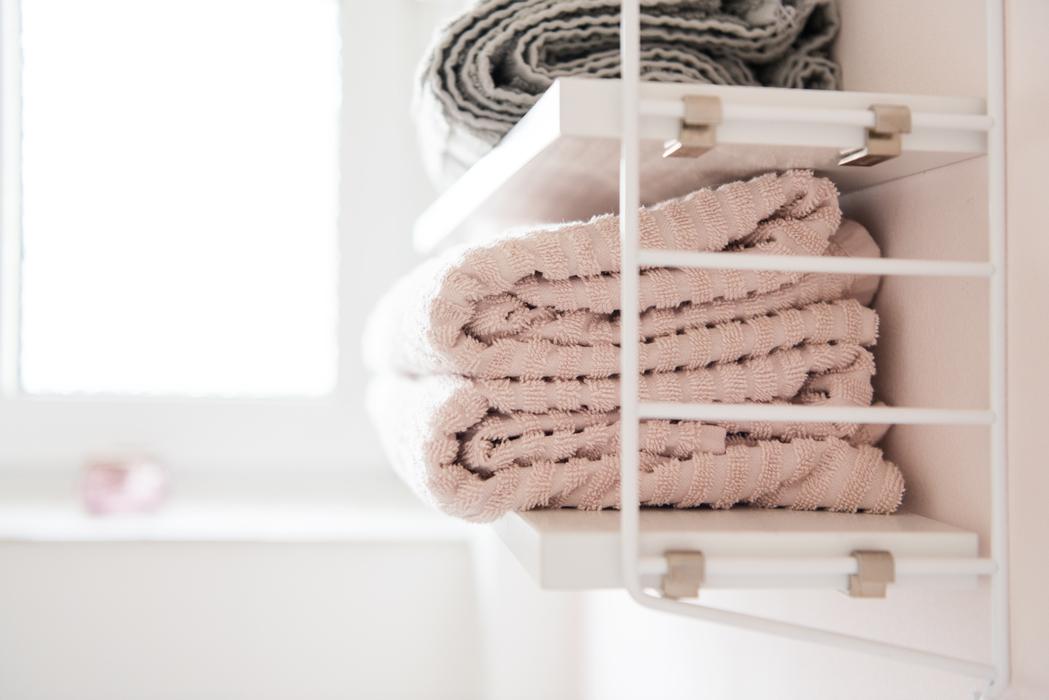Helles Badezimmer mit weißen schmalen Fliesen, rosafarbener Wand mit weißem String-Regal und rosafarbenen Handtüchern