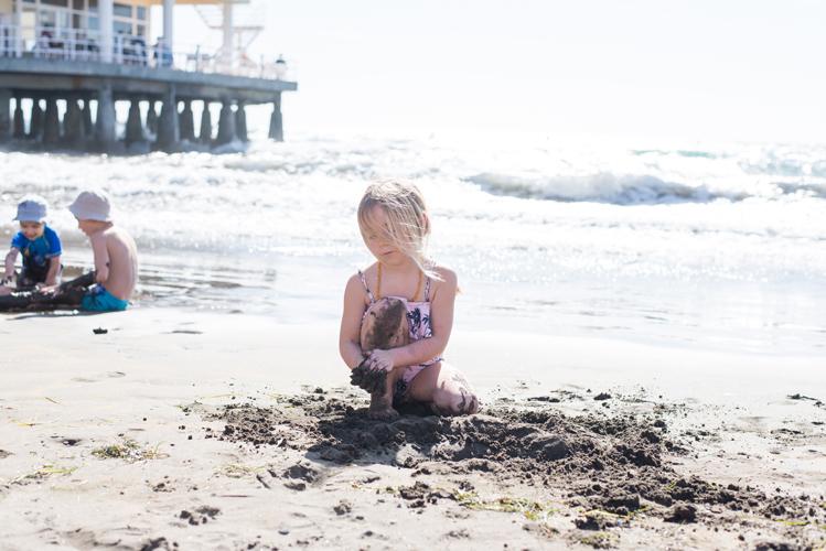 Mädchen am Stadtstrand von El Médano auf Teneriffa spielt im Sand