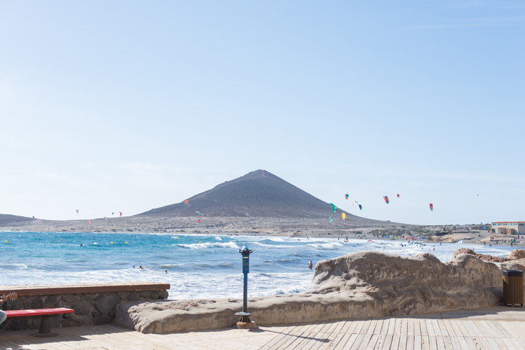 Blick auf den roten Berg bei El Médano auf Teneriffa und die Surfer