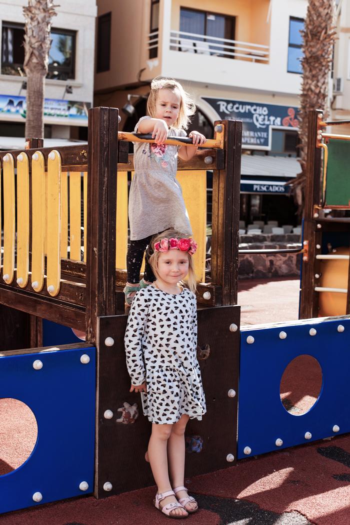 Zwei Mädchen spielen auf einem Spielplatz auf Teneriffa im Urlaub mit Blumen im Haar und Kleidern
