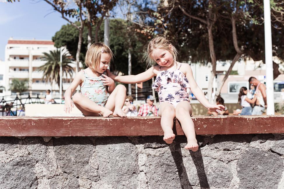 Zwei Mädchen sitzen auf der Mole am Strand