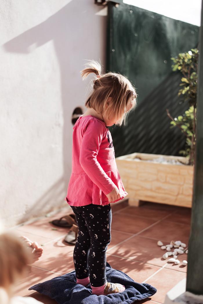Mädchen in der Unterkunft auf Teneriffa im Urlaub spielt auf der Terrasse