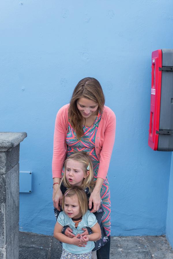 Mutter mit zwei Kindern vor einer blauen Wand in Las Galletas