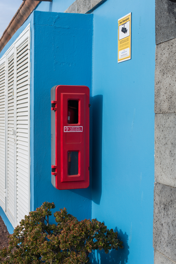 Ein roter Kasten vor einer blauen Wand in Las Galletas