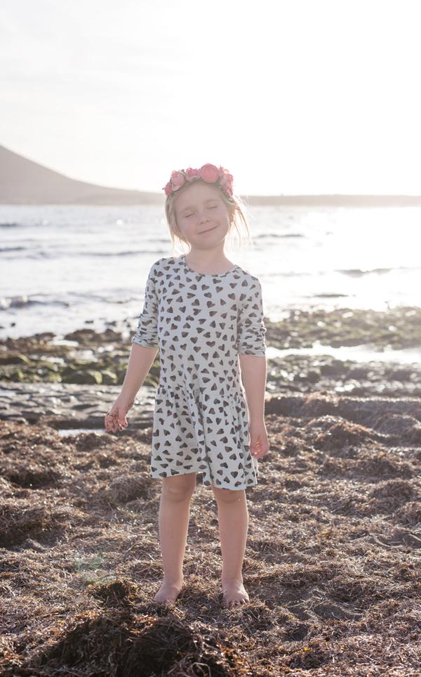 Blondes Mädchen mit Blumenkranz und blauem Kleid am Strand auf Teneriffa iim Urlaub