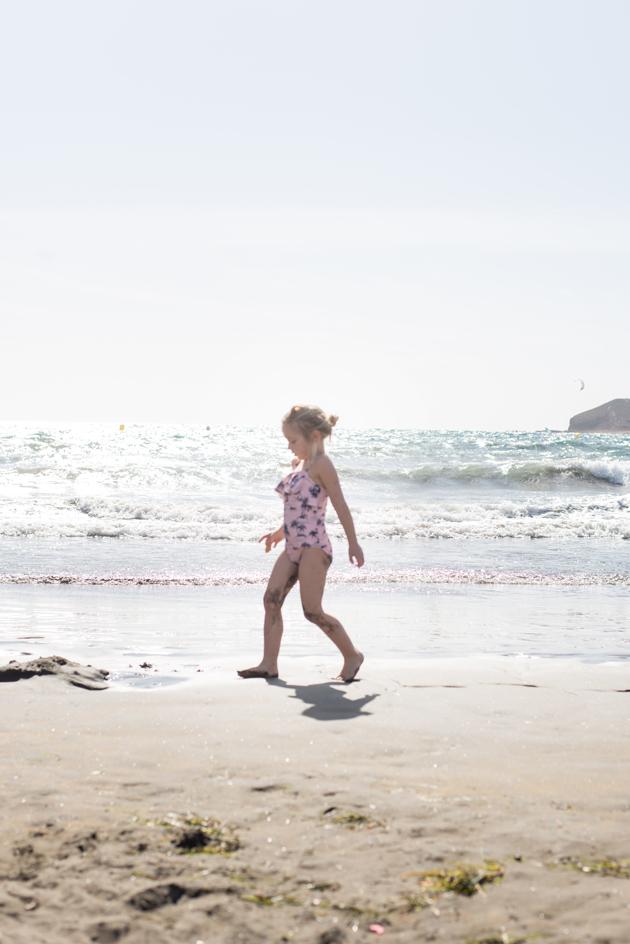 Blondes Mädchen im Badeanzug spielt am Strand auf Teneriffa im Urlaub