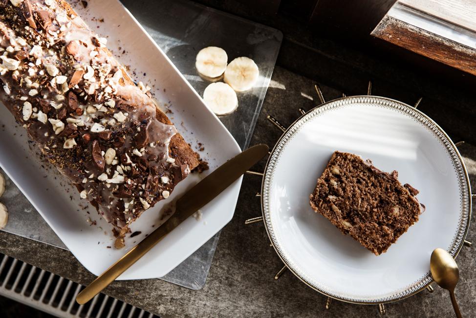 Flatlay eines Bananenbrotes mit Schokoladen-Nuss-Topping auf grauem Stein