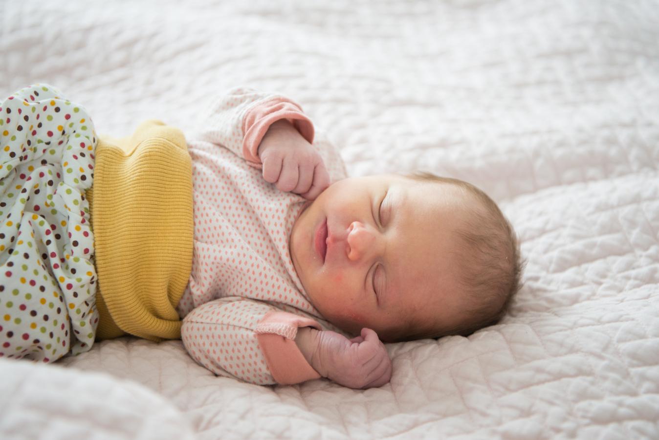 Neugeborenes Baby Mädchen, das mit Kaiserschnitt geboren wurde,liegt auf rosa Decke und schläft