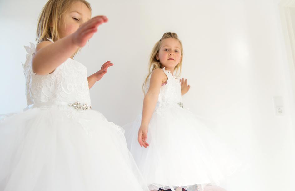 Zwei blonde Blumenmädchen tragen weiße Blumenkleider und tanzen