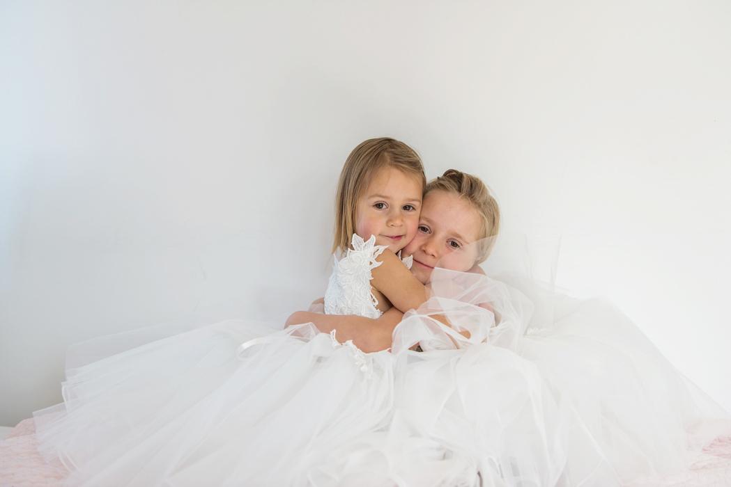 Zwei blonde Blumenmädchen tragen weiße Blumenkleider und umarmen sich