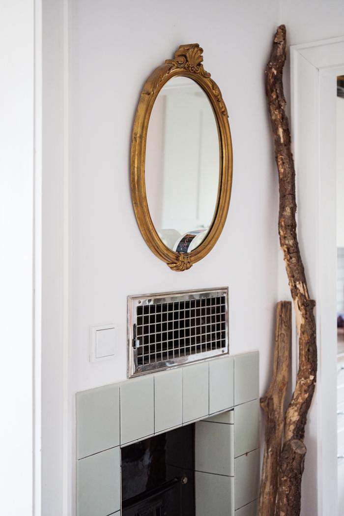 Kachelofen mit mintfarbenen Fliesen, goldenem Spiegel, Holzdeko