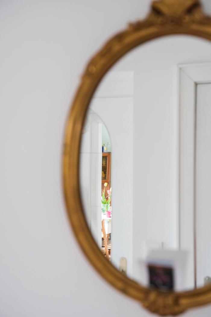 Blick in den Eingangsbereich mit weißem Tisch, roter Lampe, Kachelofen, Goldspiegel, rotem Teppich und Terrazzoboden