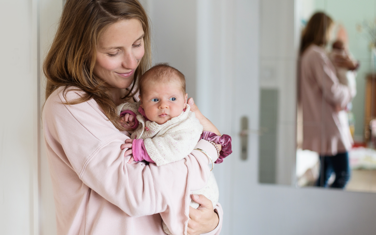 Mama hält Baby auf dem Arm im Wohnzimmer