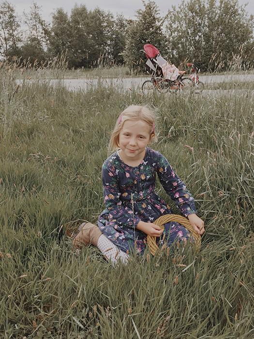 Mädchen hält Ring für Türkranz aus Gräsern auf einer Wiese