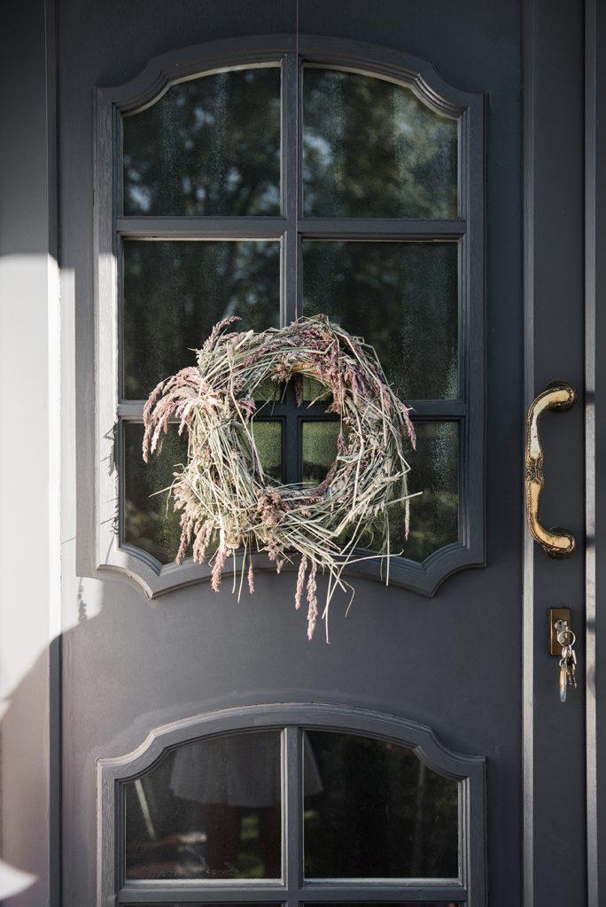 Selbstgebundener Türkranz aus Gräsern hängt an grauer Haustür auf dem Land