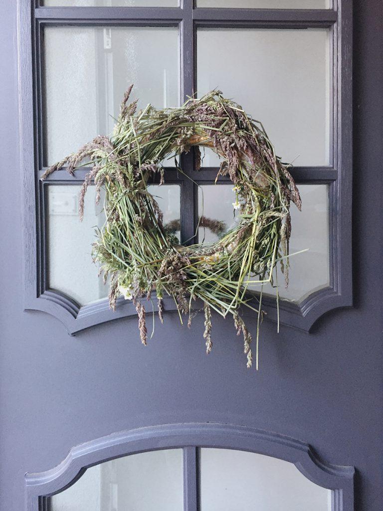 Selbstgebundener Türkranz aus Gräsern hängt an grauer Haustür
